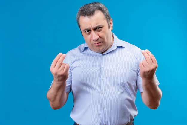 Serious middle age man in blue striped shirt gesturing with hands try to explain his point of view on a blue background