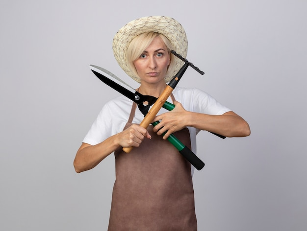Serious middle-aged blonde gardener woman in uniform wearing hat holding hedge shears and rake doing no gesture with them