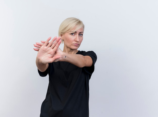 Serious middle-aged blonde slavic woman looking at camera doing stop gesture isolated on white background with copy space