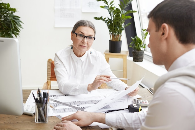 Serious middle aged female senior engineer in eyeglasses holding pencil and piece of paper and looking at young brunette employee with strict questioning expression, pointing mistakes in drawings