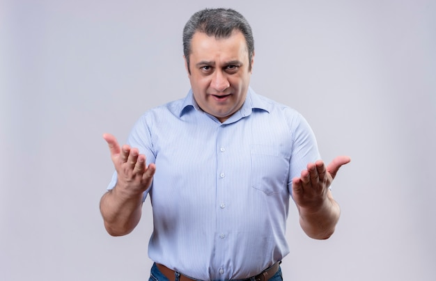 Серьезный мужчина средних лет в синей рубашке в вертикальную полоску удивлен и задает вопросы с поднятой рукой на белом фоне