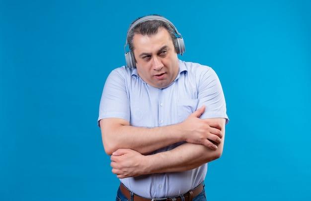 ヘッドフォンで青い縦縞のシャツを着ている深刻な中年男が青い背景に暖かく滞在しようとして冷たく感じ