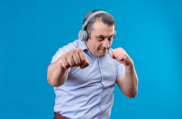 青の背景にボクシングの動きを練習するヘッドフォンで青い垂直ストライプシャツを着ている深刻な中年男