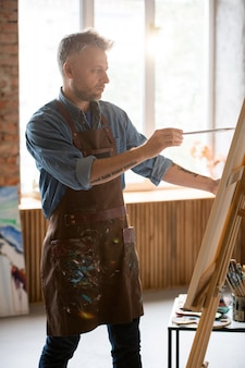 Serious middle aged man with paintbrush looking at picture on easel while painting in his workshop or studio