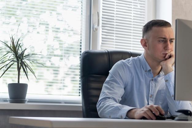 진지한 중년 남자는 사무실에서 컴퓨터로 일합니다. 감독은 그의 안락의자에 있다. 보스는 프로젝트에 집중하고 있습니다.