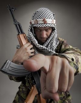 あなたを指しているak-47を持つ深刻な中東の男