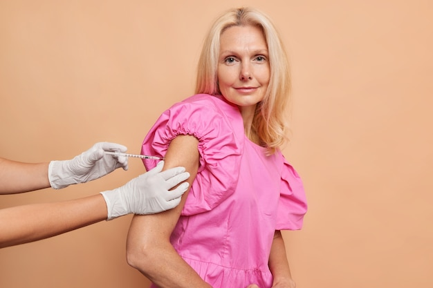 Serious middled aged woman looks directly at camera while getting covid vaccine shot wears fashionable pink dress