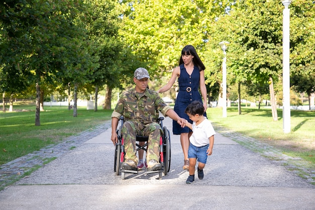 Padre militare serio che cammina in sedia a rotelle con la famiglia. papà di mezza età caucasico in uniforme del camuffamento che tiene la mano del figlio e parla con la moglie graziosa. veterano di guerra e concetto di disabilità