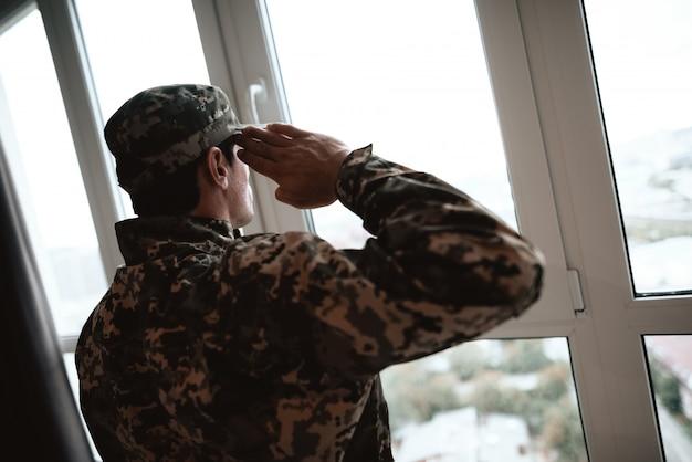窓の近くの深刻な軍服敬礼。