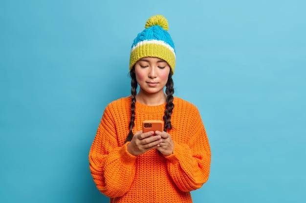 スマートフォンのディスプレイに集中しているピグテールを持つ深刻なミレニアル世代の女の子は、ワイヤレスインターネットを使用してファッショナブルな冬の服を着て青い壁に隔離された友人とのオンラインチャットを手配します