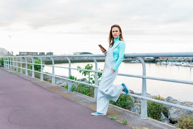 海沿いの港でスマートフォンを保持している深刻なミレニアル世代の若い成人女性