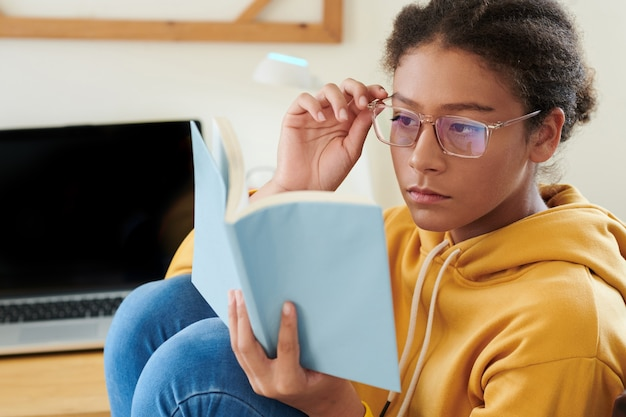 Serious mixed race school girl sitting at desk with laptop and adjusting eyeglasses while reading book and preparing for lesson
