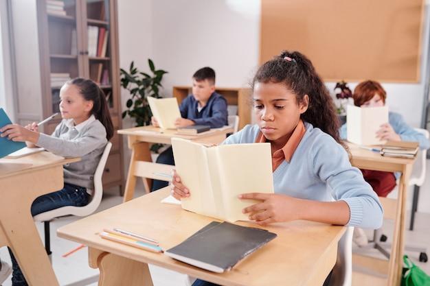 Серьезная школьница смешанной расы и группа ее одноклассников за другими партами читают книги, работая индивидуально на уроке в классе