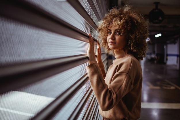 Serious mixed race trap girl standing next to garage door