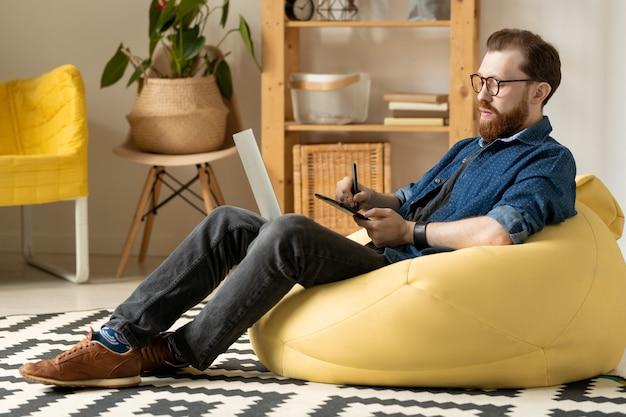 自宅でビーンバッグに座って、スケッチに取り組んでいる間、描画パッドを使用して眼鏡をかけた真面目な現代の若いひげを生やしたデザイナー