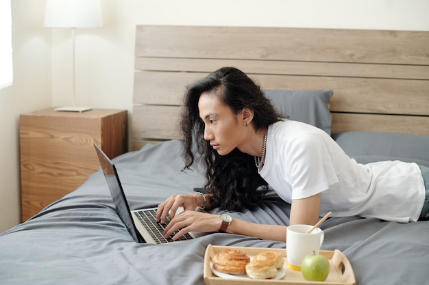 Serious modern young vietnamese guy in white tshirt working with laptop remotely while lying in bed with breakfast on tray