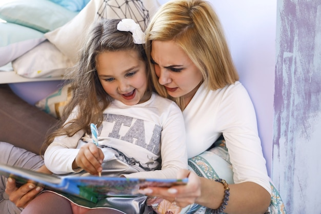 Серьезная мама и улыбающаяся дочь пишут в тетради в светлой комнате