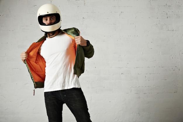 白で隔離のヴィンテージヘルメットを身に着けている彼のカーキ色のジャケットのオレンジ色の裏地を示す深刻なモーターサイクリスト