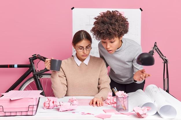 真面目な多文化の女性は、bluenrpintに焦点を当てた共通の戦略を見つけようとします。オフィスの机の上の紙をくしゃくしゃにして、スタートアッププロジェクトの紙のレポートのブレインストロームを分析してアイデアについて話し合います。チームワークの概念
