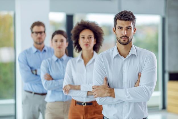 팔을 넘어 서서 사무실에 서있는 동안 카메라를보고있는 사업 사람들의 심각한 다민족 그룹