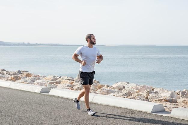 Serious muscular man running on seaside road