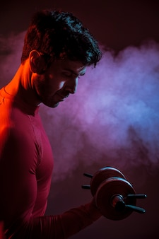 Serious muscular man with dumbbell in dark