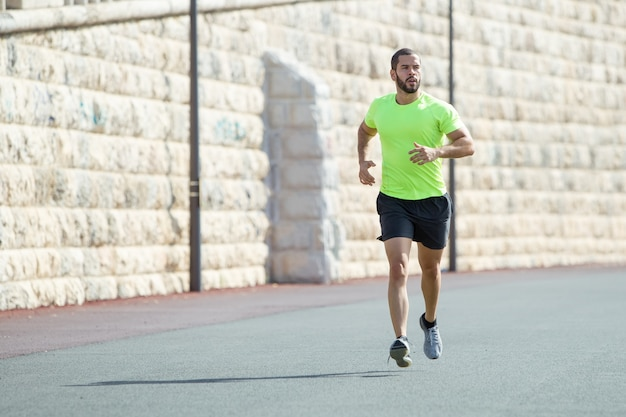 Serious muscular sporty man running on road