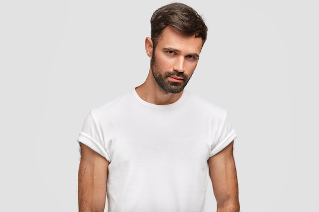 黒い無精ひげ、髪、カジュアルな白いtシャツを着た、真面目な筋肉質の若い男性は、筋肉質の体を持ち、白い壁に隔離された何かを注意深く聞いています。無精ひげを生やした男は屋内に立っています