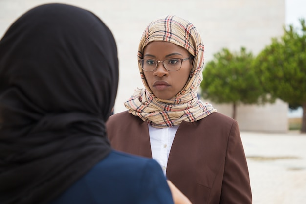 Serious muslim female employee talking to colleague