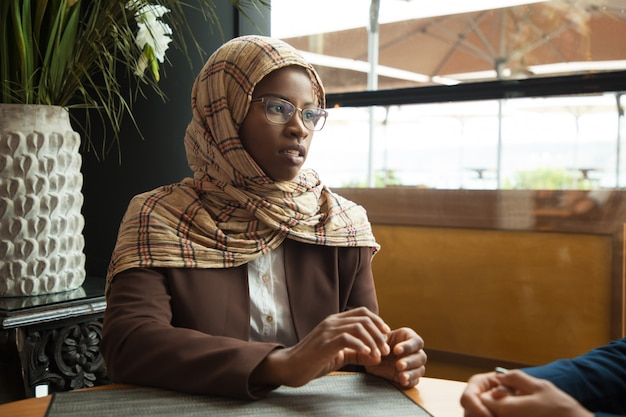 Serious muslim female employee talking to coworker