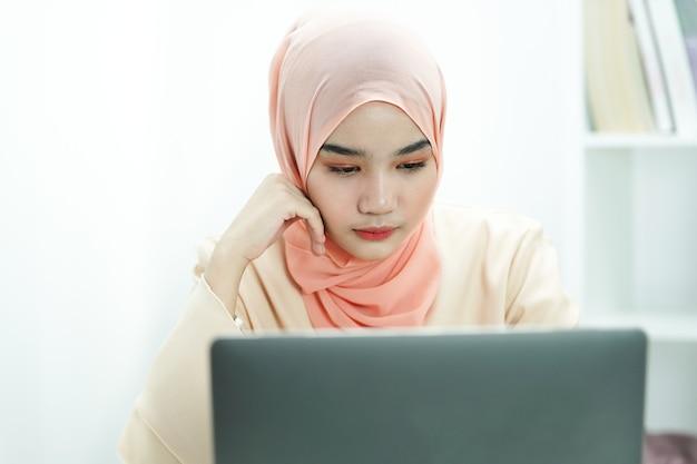 Серьезная мусульманская студентка девушка готовится к экзамену или курсовой работе, делает домашнее задание.