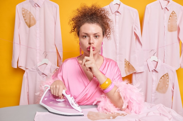 Serious mysterious housewife with curly hair makes silence gesture asks not to tell anyone she burnt shirt while ironing as has lack of experience wears dressing gown isolated over yellow wall.