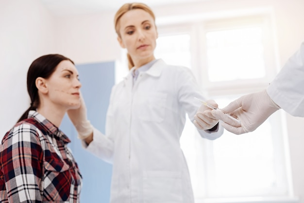 주사기를 들고 환자 앞에 서있는 동안 보톡스 주사를하려고하는 심각한 경험이 풍부한 의사
