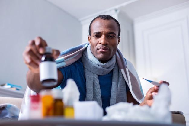 体温計を持ち、薬を飲みながらボトルを持っている深刻な素敵な病気の人