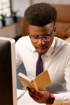 彼の毎日のスケジュールを計画しながら彼のメモを勉強している深刻ないい男