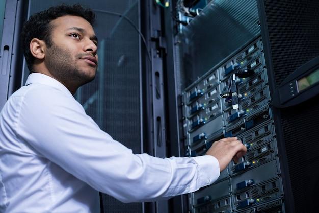 Серьезный приятный молодой человек протягивает руки и намеревается нажать кнопку во время работы с информационными технологиями