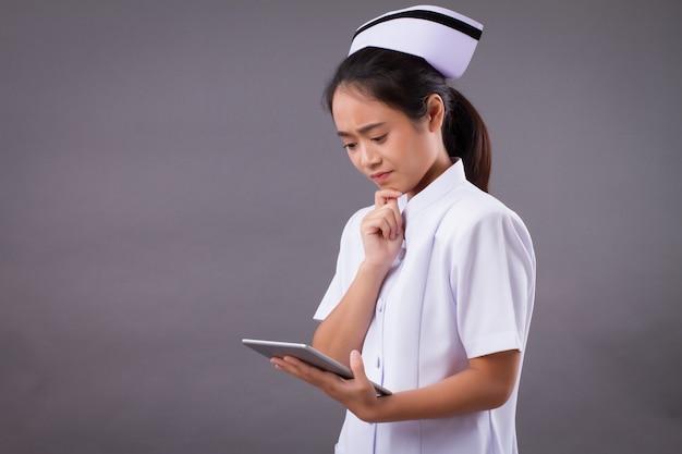 Серьезная медсестра с помощью цифрового планшета