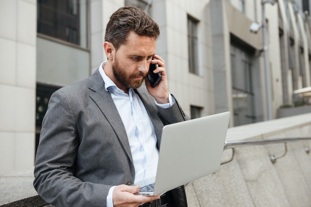 銀色のラップトップに取り組んでいるとビジネスセンターの近くに立っている間携帯電話で話している古典的なスーツの深刻なオフィスをもつ男
