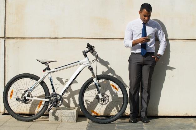 Serious office worker near bike reading message