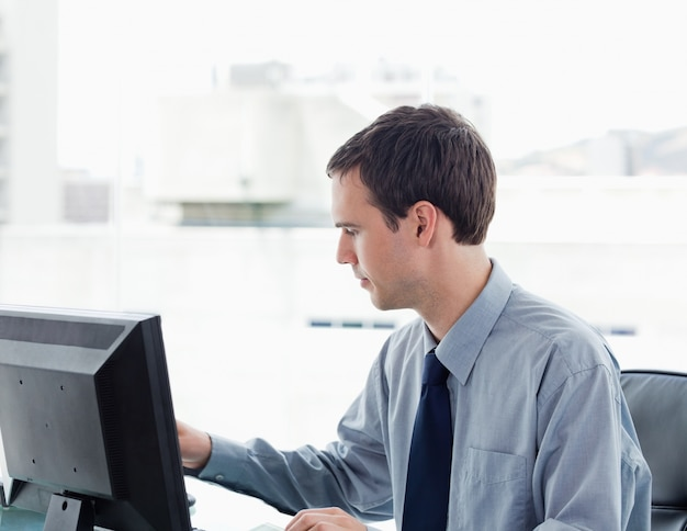 Serious office worker using a monitor
