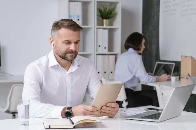 Серьезный офисный работник с сенсорной панелью, смотрящий на дисплей во время онлайн-обучения, конференции или вебинара