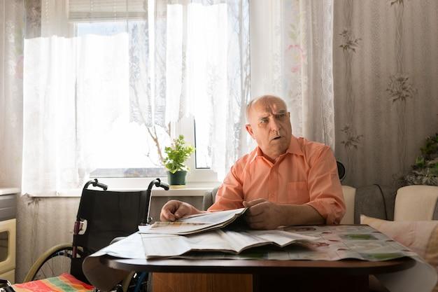 오른쪽 프레임을 보면서 신문을 들고 테이블에 앉아 있는 오렌지 셔츠를 입은 심각한 대머리 남자.