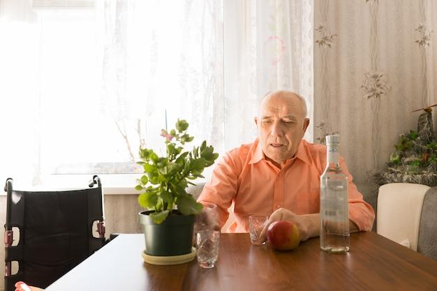 ワインボトル、赤いリンゴと小さな緑の植物とテーブルに座っている深刻な老禿げた男
