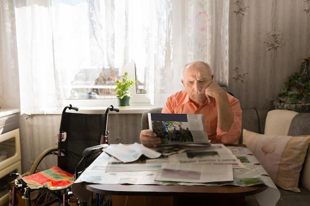 車椅子を横にして居間で休んでいる間、タブロイド紙のニュースを真剣に読んでいる真面目な老人。