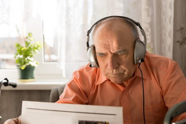 彼の家の中で新聞を読んでヘッドセットデバイスを持つ深刻な老人。