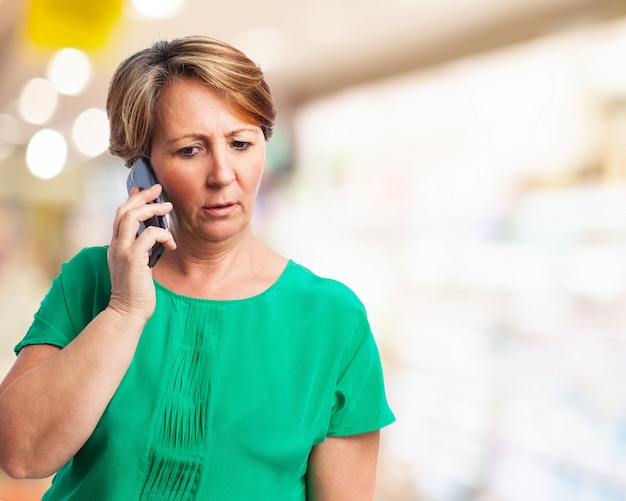 Serious older woman talking on the phone