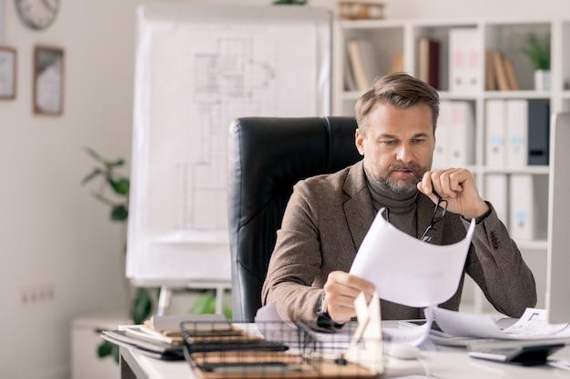オフィスの机のそばの肘掛け椅子に座って紙のスケッチを見て深刻なまたは物思いにふける成熟した建築家