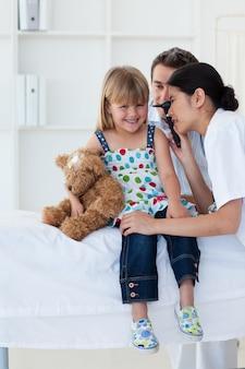 深刻な患者が少女の耳を検査する