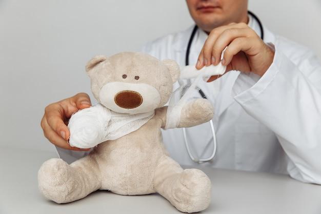 Серьезный педиатр перевязывает плюшевого мишку в медицинском кабинете