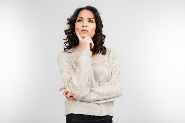 Serious pensive brunette girl on a gray studio background with copy space